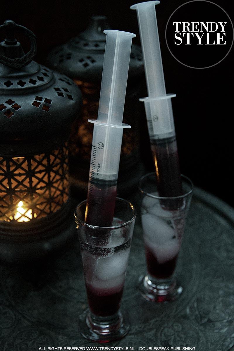 Halloween cocktail met injectiespuit met 'bloed'